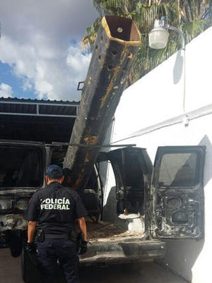 In this Sept. 17, 2016, photo released by Mexico Federal Police, an officer stands next to a van outfitted with a 10-foot (3-meter) air cannon in Agua Prieta, Mexico, along the border with Douglas, Arizona.