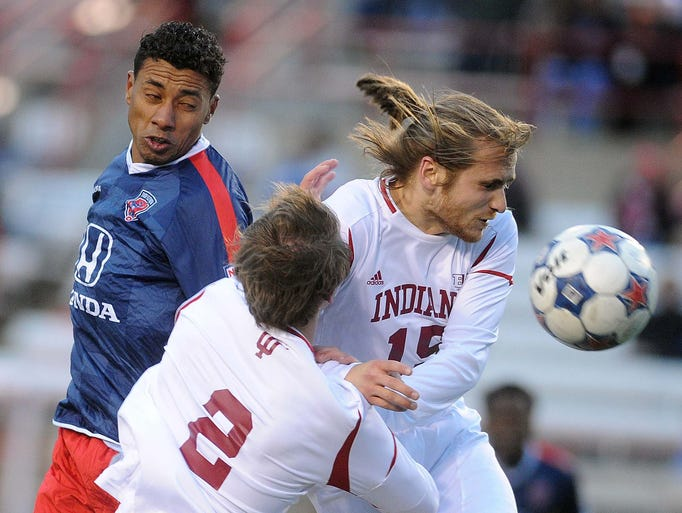 Kleberson of the Indy 11, left, heads the ball toward the goal as IU players Bill McConnell and Jamie Vollmer defend. The Indy Eleven played Indiana University in Indy's final pre-season game at Carroll Stadium at IUPUI Friday April 4, 2014.