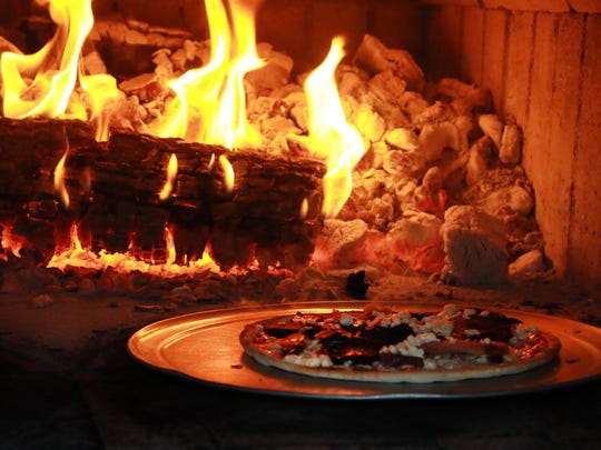 A pizza cooks in one of the wood-fired ovens at Stoney