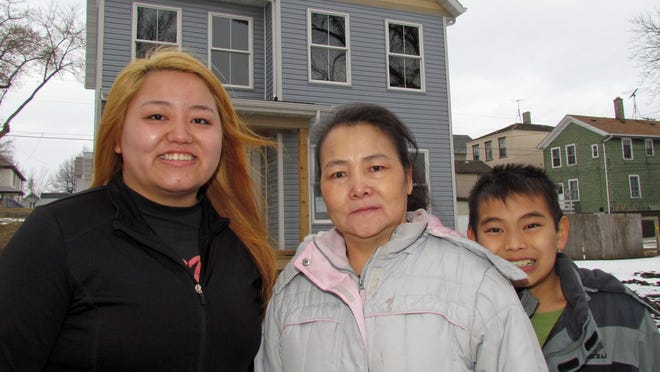 From left, Pa Kou, 22, Dia Chang and Jacky Chang, 12, stand before their new home on Erie Avenue. The home, which is not yet completed, is a Sheboygan Gateway project with the Habitat for Humanity Lakeside.