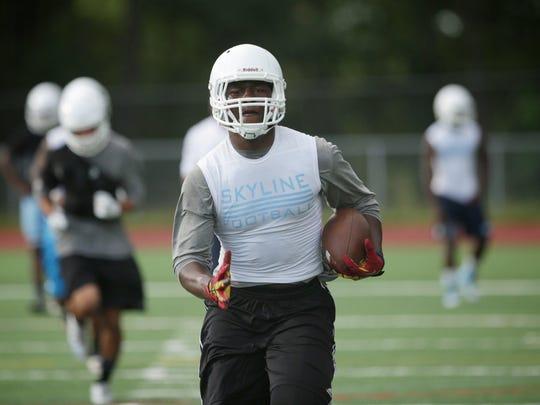 Ann Arbor Skyline High School linebacker Daelin Hayes, 17, of Ann Arbor, runs through drills during practice on Tuesday, August, 11, 2015, in Ann Arbor, MI.