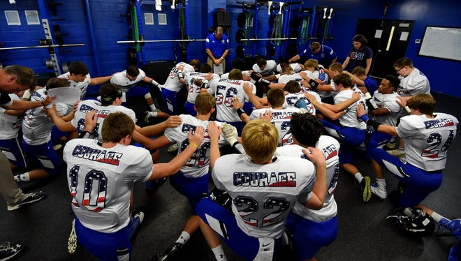 The St. Joseph's Catholic School football team, wearing special uniforms for Military Night, prays before a game against Woodruff Sept. 9.The Knights are 2-7 heading into Friday's season finale against Walhalla.