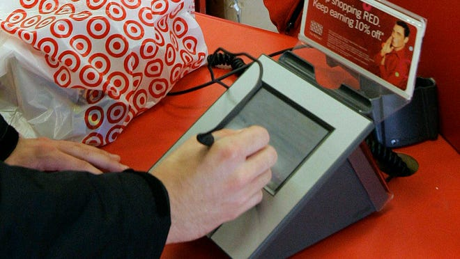A customer signs his credit card receipt at a Target store.