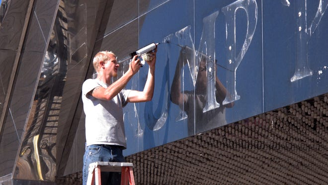 A worker applies caulk to holes in the facade of the former Trump Plaza casino in Atlantic City N.J. after letters spelling out the casino's name were removed on Monday Oct., 6, 2014. The removal came after Donald and Ivanka Trump prevailed upon the casino's parent company to strip their name from it as part of a lawsuit seeking similar dissociation from the Trump Taj Mahal, and the Trump Entertainment Resorts company.(AP Photo/Wayne Parry)