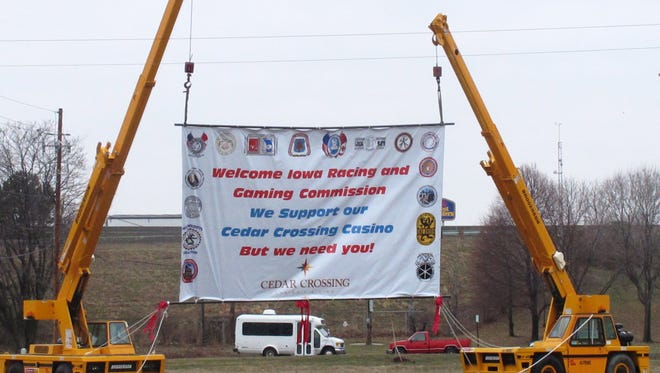 Cranes hold up a banner with a message to the Iowa Racing and Gaming Commission at the site of a proposed casino in Cedar Rapids, Iowa on Thursday, April 3, 2014. (AP Photo/Ryan J. Foley)