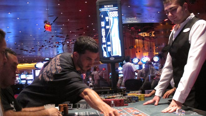 A dealer watches as gamblers place bets on a roulette table at the Revel Casino in Atlantic City.