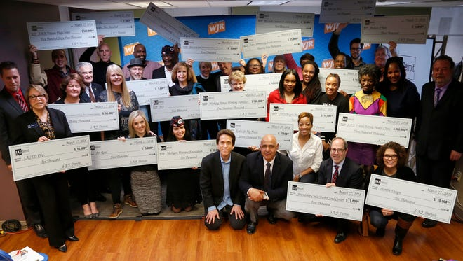 Twenty-two charities along with Mitch Albom and Dr. Chad Audi gather for a portrait after S.A.Y. Detroit distributed checks at the Fisher Building in Detroit on Tuesday, March 27, 2018.