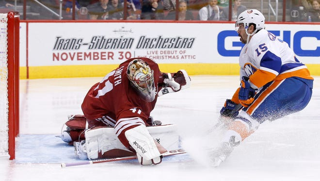 Arizona Coyotes' Mike Smith (41) makes a save on a shot by New York Islanders' Cal Clutterbuck (15) during the third period of an NHL hockey game Saturday, Nov. 8, 2014, in Glendale, Ariz. The Islanders defeated the Coyotes 1-0.