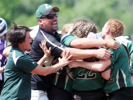 Laconia head coach Scott Ritzema has a group hug after