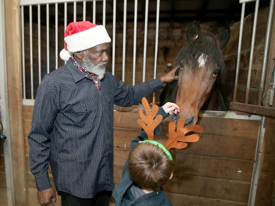 Kenneth Brown shows a foster child a horse at The Riding