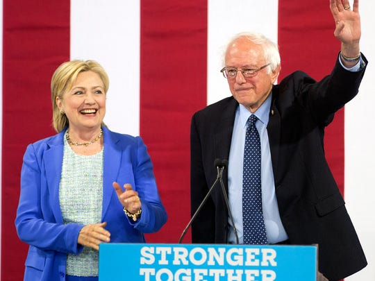 Democratic presidential candidate Hillary Clinton smiles as she arrives on stage with Sen. Bernie Sanders, I-Vt., Tuesday, July 12, 2016, in Portsmouth, N.H. Sanders announced his endorsement for Clinton.