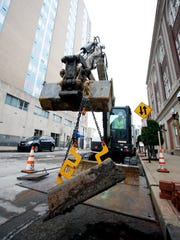 A crew from MSD replaces a catch basin at the corner of 3rd and Guthrie. The basin, made of brick from the late 1800s, has broken down causing a cave in.Jan. 13, 2017
