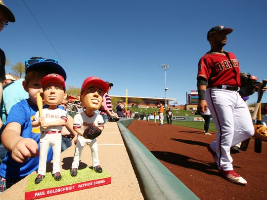 A child plays with Arizona Diamondbacks bobbleheads as a player walks by during spring training on Mar. 2, 2017, at Salt River Fields near Scottsdale.
