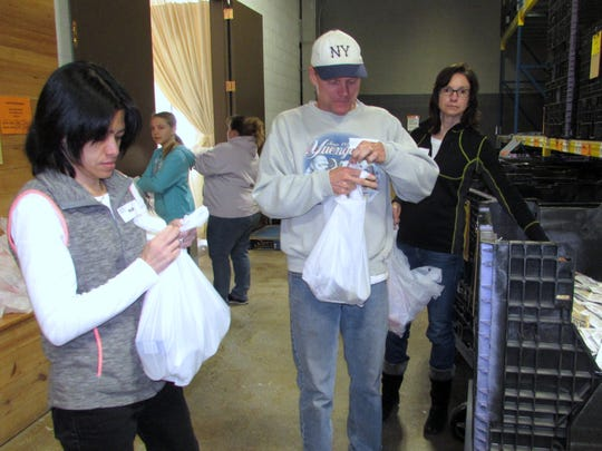 Maria Kurniawan, left, of Big Flats, and other volunteers pitch in Monday at the Food Bank of the Southern Tier.