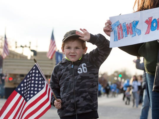 Xavier Stilin, 5, and his mother Suzie Stilin, stand with a hand-made sign colored by Xavier during the Four Freedoms Veterans Day Parade on West Franklin Street in Evansville, Ind., on Saturday, Nov. 11, 2017. Xavier's uncle is a 21-year veteran of the United States Marine Corps.
