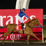 Silvestre De Sousa knows his position as he salutes the crowd while crossing the finish line first aboard African Story in the Dubai World Cup on Saturday.