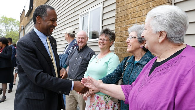 Republican Dr. Ben Carson greets well wishers Tuesday after a brief stop at the His Hands Free Clinic in Cedar Rapids.