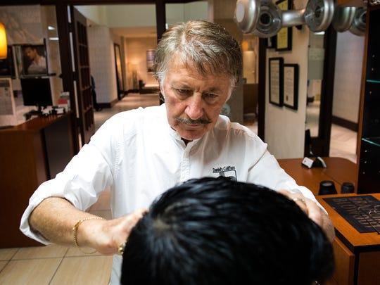 Daniel Ruidant cuts Alex Vasquez's hair in his shop Daniel's Coiffure on Wednesday, Aug. 9, 2017.