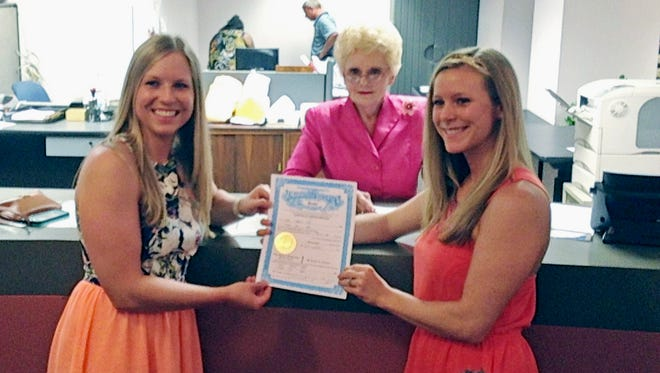 """Laurin Locke, 24, right, and her partner Tiffany Brosh, 26, display their marriage license as Hinds County Circuit Clerk Barbara Dunn, center, joins them, Monday, June 29, 2015, in Jackson, Miss. The couple were able to marry after Attorney General Jim Hood emailed the state's 82 circuit clerks saying he would not take """"adverse action"""" against any clerk who issued a marriage license to a same-sex couple."""