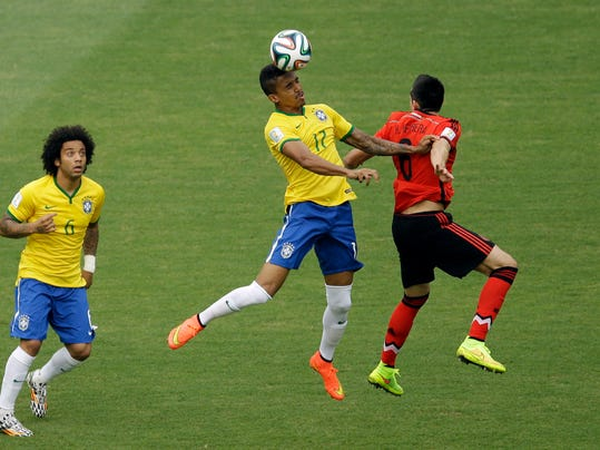 Brazil's Marcelo, left, looks on a Brazil's Luiz Gustavo and Mexico's Hector Herrera, right, go for a header during the group A World Cup soccer match between Brazil and Mexico at the Arena Castelao in Fortaleza, Brazil, Tuesday, June 17, 2014.  (AP Photo/Themba Hadebe)