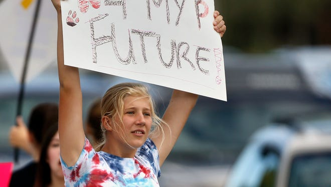 Pamona High School student Ciana Vrtikapa holds up a sign to passing motorists in a busy intersection near her school.