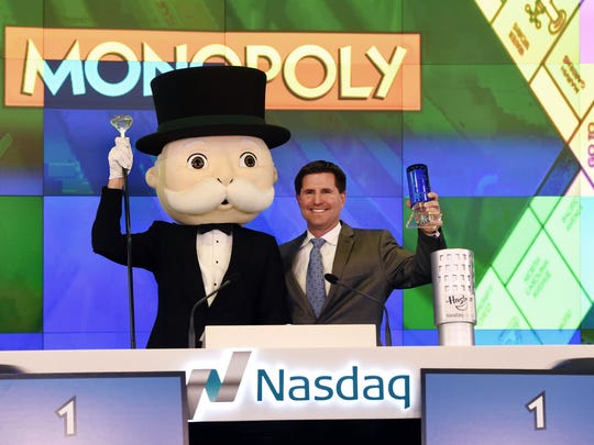 """Mr. Monopoly and Hasbro senior vice president of global brand strategy and marketing, Eric Nyman celebrate after ringing the Nasdaq's closing bell at the Nasdaq MarketSite on Thursday. The event marked the 80th anniversary of 1935 publication of the board game """"Monopoly"""" by Parker Brothers, before the company's 1991 purchase by toy manufacturer Hasbro Inc."""