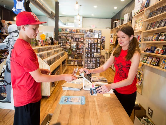 Ben Boodrum, 13, buys a pack of cards from sales assistant Morgan Albritton after school April 27 at Haywood Comics in West Asheville. May 7 marks Free Comic Book Day across the country, and Haywood Comics will be giving away comics, gift cards, and more.