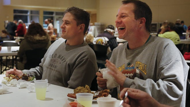 "Luke Johnson and Brian Cronk share a laugh at the ""Celebrate Recovery"" Thanksgiving dinner at Hope Lutheran Church in West Des Moines on Thursday."