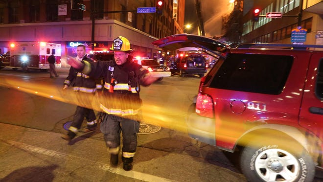 Firefighters urge onlookers to step back while battling the devastating fire at the former Younkers building early on March 29.