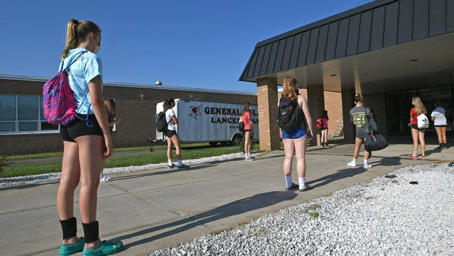 Keeping more than 6 feet apart, volleyball players wait to enter the gym and have their temperature checked on July 9 before a workout at General McLane High School. Athletes training this summer are encountering some of the protocols that will be in place when classes are scheduled to resume.