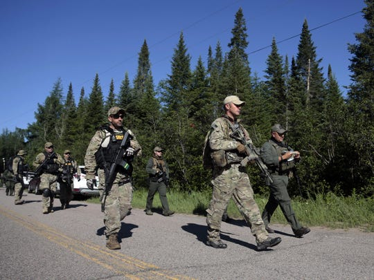 Law enforcement officers walk along a road June 24 before going into the woods near Mountain View, New York, during the search for Richard Matt and David Sweat, two escaped prisoners from Clinton Correctional Facility. Matt was shot and killed Friday, June 26, and Sweat was shot and captured Sunday.