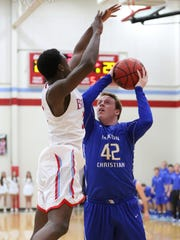 Jackson Christian's Garrett Hopkins tries to shoot over USJ's Brandon Craig on Saturday.