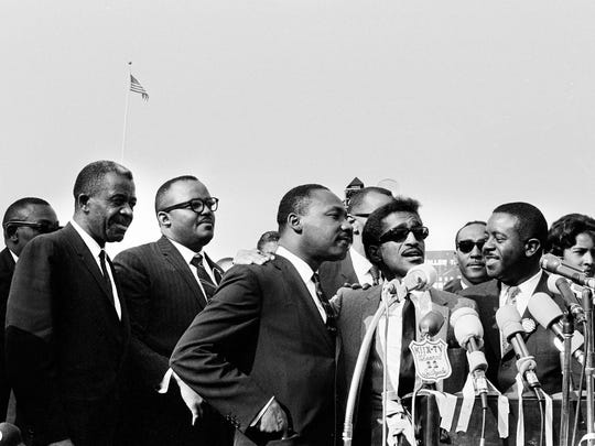 Entertainer Sammy Davis Jr., center in sunglasses, stands, between Dr. Martin Luther King Jr., left and Ralph Abernathy, right, on the platform at a mass civil rights rally at Wrigley Field in Los Angeles on May 26, 1963. Dr. King was joined by several other leaders of the Birmingham integration movement. Davis told the crowd that he will give on week's salary in Las Vegas, about $20,000, to the cause.