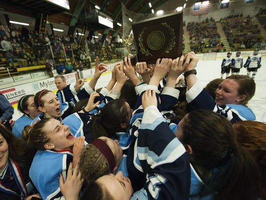Mount Mansfield celebrates with the championship trophy during the Division II high school girls hockey state championship between the MMU Cougars and the U-32 Raiders at Gutterson Fieldhouse on Wednesday night.