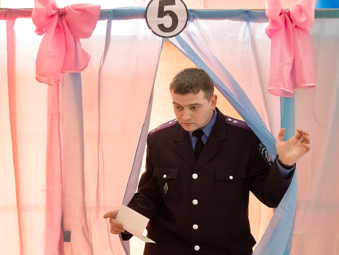 An Ukrainian police officer exits a voting booth after casting his vote in Perevalne, Ukraine, on March 16, 2014. Residents of Ukraine's Crimea region are voting in a contentious referendum on whether to split off and seek annexation by Russia.