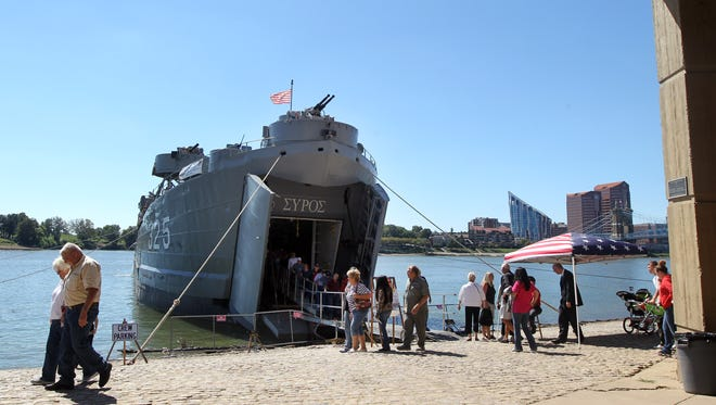 Visitors disembark from the World War II ship LST (Landing Ship Tank) 325 is which is moored at the public landing and open for tours.