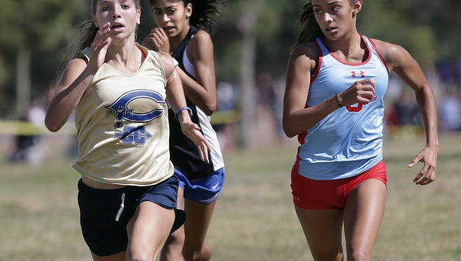 Socorro's Natalie Gomez glances over as Coronado's Jennelle Jaeger-Darakjy passes her in the last 50 meters Saturday in the District 1-6A Cross Country Championships at the Chamizal National Memorial. Jaeger-Darakjy won with a time of 19:25.39.