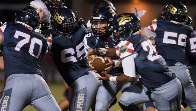 Gulf Breeze Quarterback, Dylon Kelley, (No. 5) gives running back, Carl Taylor,(No. 25) the handoff during Friday night's game against Navarre High School.