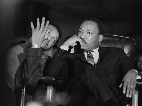 Dr. Martin Luther King Jr., seated with aide Jesse