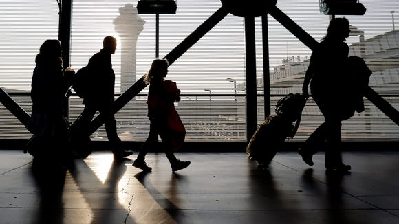 In this file photo from Dec. 1, 2013, travelers walk