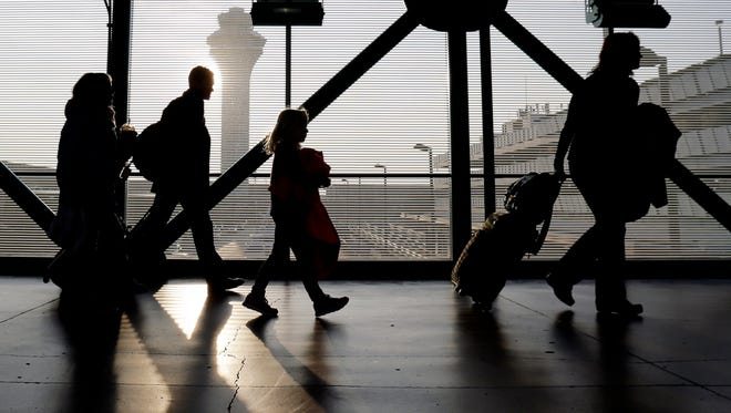 In this file photo from Dec. 1, 2013, travelers walk through Terminal 3 at O'Hare International airport in Chicago.