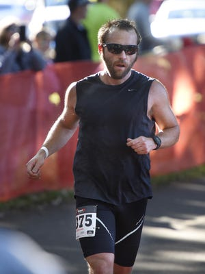 Douglas Johnson crosses the finish line as the first half-marathon finisher during Saturday's Graniteman Mississippi River Run at Municipal Park in Sauk Rapids.