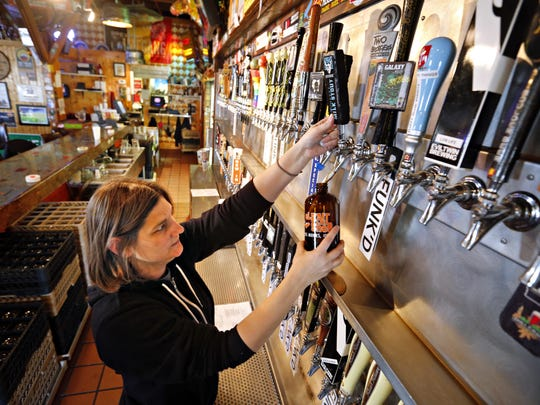 Bartender Teresa Ceretti pours a growler of Stone coffee milk stout at El Bait Shop.
