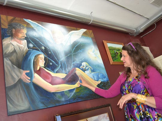 Rose Lucas-Haninger describes her realistic depiction of Christ's birth in her painting hanging in The Painted Rose Gallery. Her paintings range from serene landscapes to emotional illustrations of her faith.
