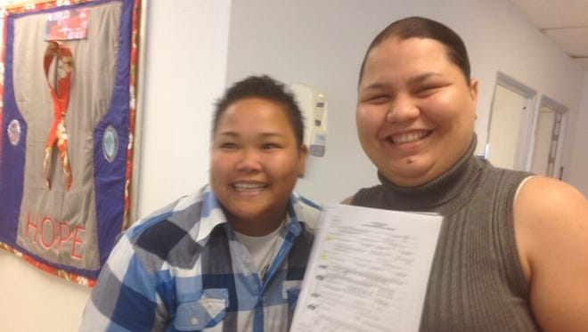 Loretta M. Pangelinan, left, and Kathleen M. Aguero are all smiles just after receiving their marriage license Tuesday morning.