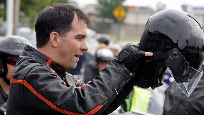 Wisconsin Gov. Scott Walker puts on his helmet before riding his Harley-Davidson in Sheboygan in July 2014.