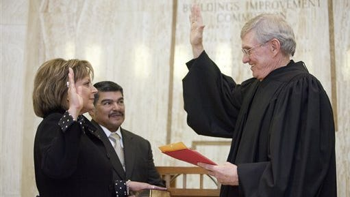 Chuck Franco, center, holds a Bible as his spouse, New Mexico Gov. Susana Martinez, takes the oath of office in Santa Fe on January 1, 2011.