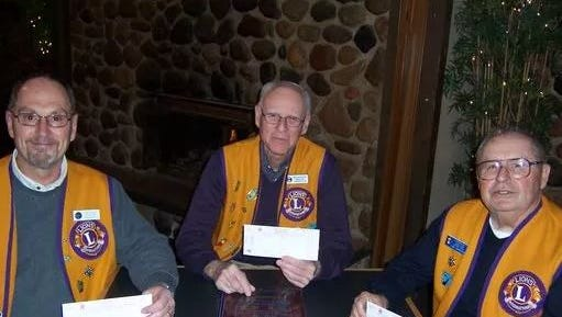Sturgeon Bay Lions Club members hold rose sale orders while they pose for a photo.