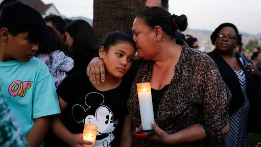 Betty Rodriguez, right, comforts her granddaughter Giselle during a prayer service held to honor the shooting victims at North Park Elementary School, Monday, April 10, 2017, in San Bernardino, Calif. A man walked into his estranged wife's elementary school classroom in San Bernardino and opened fire on Monday.