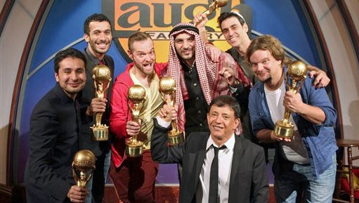 In this Oct. 21, photo provided by The Laugh Factory, the five finalists and one alternate in an international search to find the world's funniest person pose with Laugh factory impresario Jamie Masada. front kneeling, after being selected following an online competition at the The Laugh Factory in Los Angeles. Standing from left are Saad Haroon of Pakistan, Mustapha El Atrassi of France, Archie Bezos of Spain, Nitin Mirani of the United Arab Emirates, Lioz Shem Tov of Israel, and Ismo Leikola of Finland. Lioz Shem Tov, who finished sixth, will participate if one of the others cannot. The finalists were determined by online voters who saw 10 comics take the stage at the Laugh Factory in Hollywood during a Monday night jokefest that was streamed on the club's website.